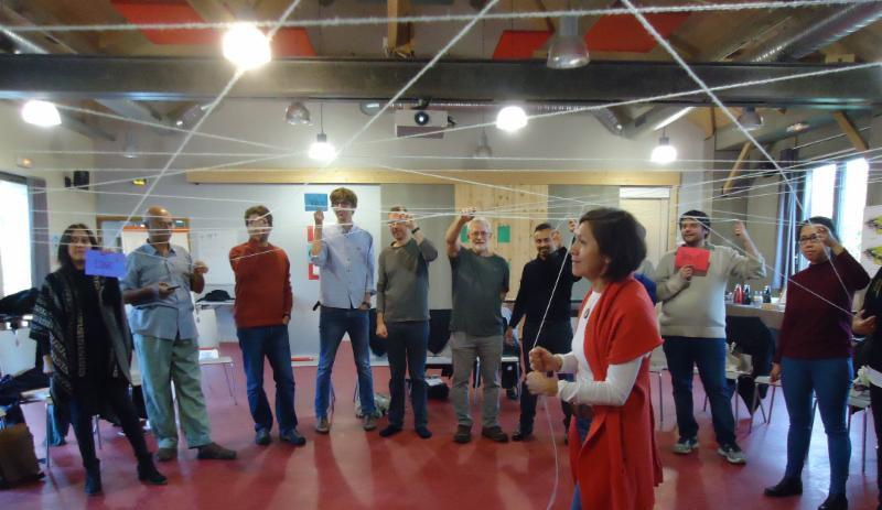 During an interactive exercise led by Michelle Mascarenhas-Swan, GEL participant Angela Martinez demonstrates the interdependence of global systems.